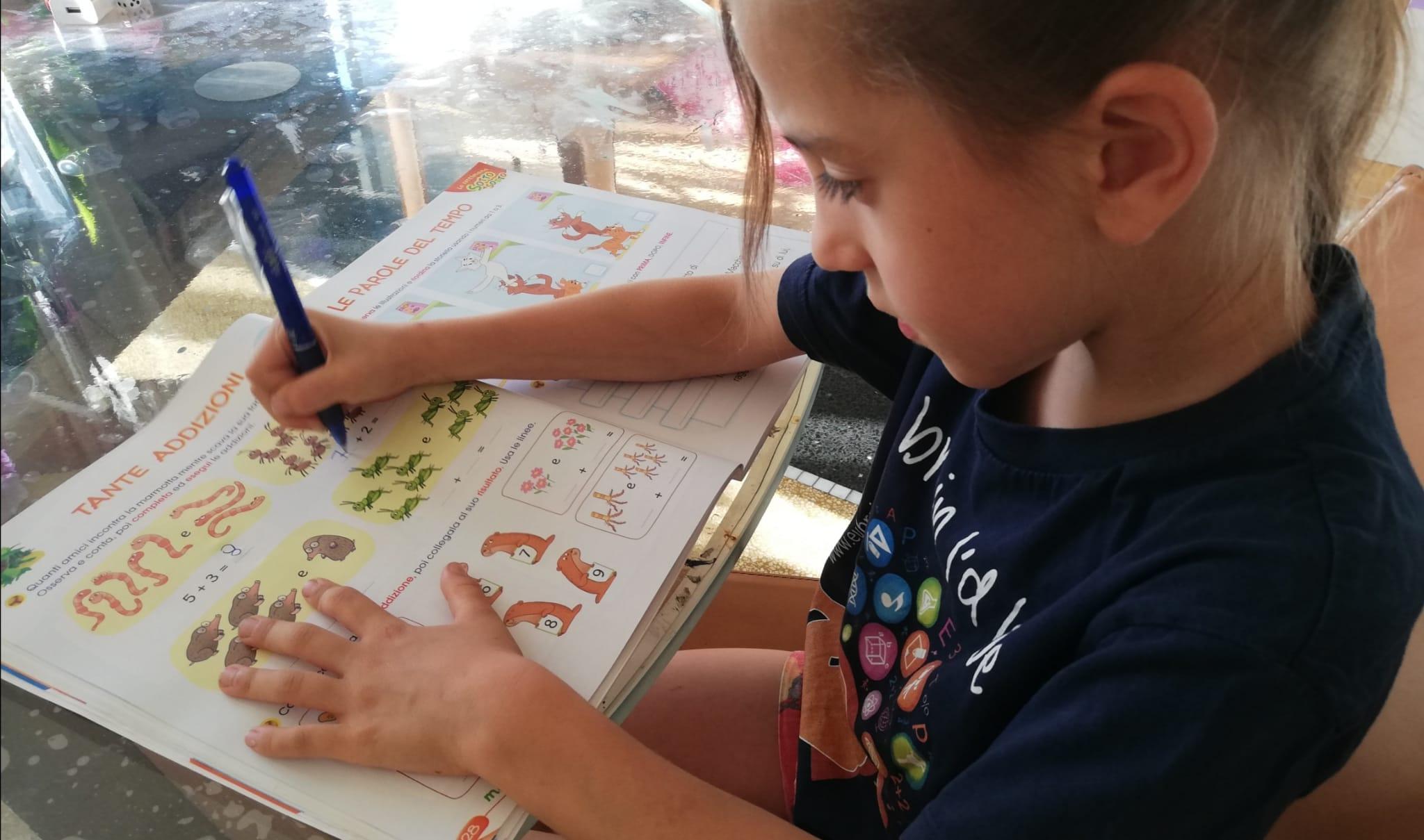 una bambina sta facendo i compiti